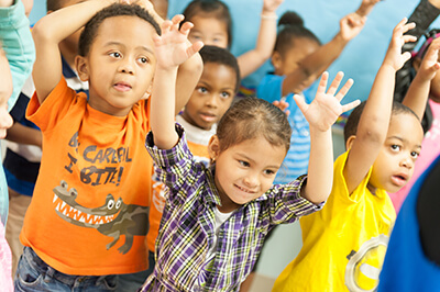 Children with their hands up in colorful t-shirts