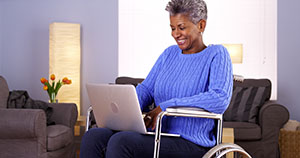 Elderly Woman in a wheelchair using a Laptop